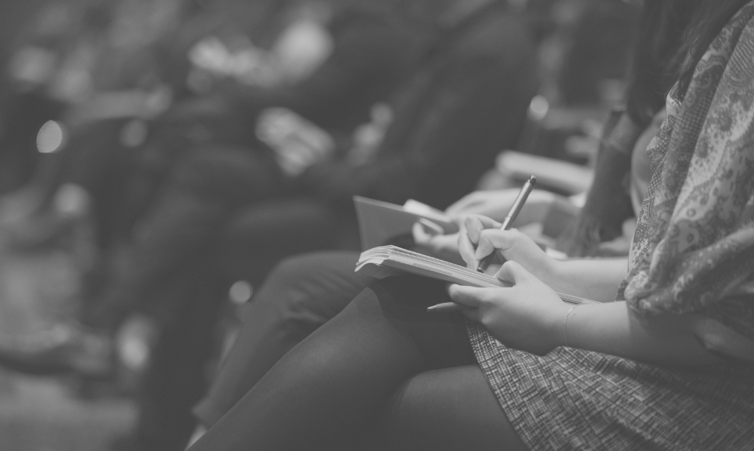 Picture of people taking notes at a conference.